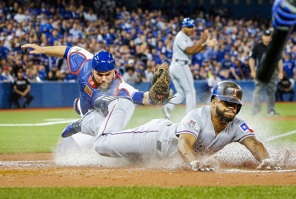 Texas Rangers' Delino DeShields slides safe into home plate past Toronto Blue Jays' catcher Russell Martin during third inning of game one American League Division Series play Oct 8, 2015 in Toronto.