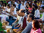 """17 MARCH 2018 - BANGKOK, THAILAND:  People pray during a """"sticky rice merit making"""" in Lumpini Park in Bangkok. Sticky rice merit making is a merit making in the Isan / Lao style, when people present small amounts of cooked sticky rice (also known as glutinous rice) to Buddhist monks. Isan is the northeast region of Thailand.     PHOTO BY JACK KURTZ"""