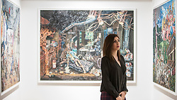 """© Licensed to London News Pictures. 22/04/2015. New Bond Street, London. A Sotheby's staff member stands in front of works unveiled by London-based artist Henry Hudson, using Plasticine as a medium, entitled """"The Rise and Fall of Young Sen - The Contemporary Artist's Progress"""" at Sotheby's.  The series follows the plight of Young Sen, from his home in rural China, to his rise on the international art scene and his eventual demise embroiled in a world of drugs, vice and the darkest corners of global politics. Photo credit : Stephen Chung/LNP"""