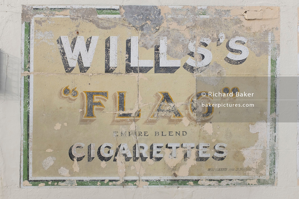 A detail of old advertising for a cigarette brand from decades ago called Will's whose product was 'Flag Empire Blend', on 19th July 2020, in Whitstable, Kent, England. W.D. & H.O. Wills was a British tobacco importer and manufacturer formed in Bristol, England. W.D. & H.O. Wills was founded in 1786 and was the first UK company to mass-produce cigarettes. It was one of the founding companies of Imperial Tobacco along with John Player & Sons.