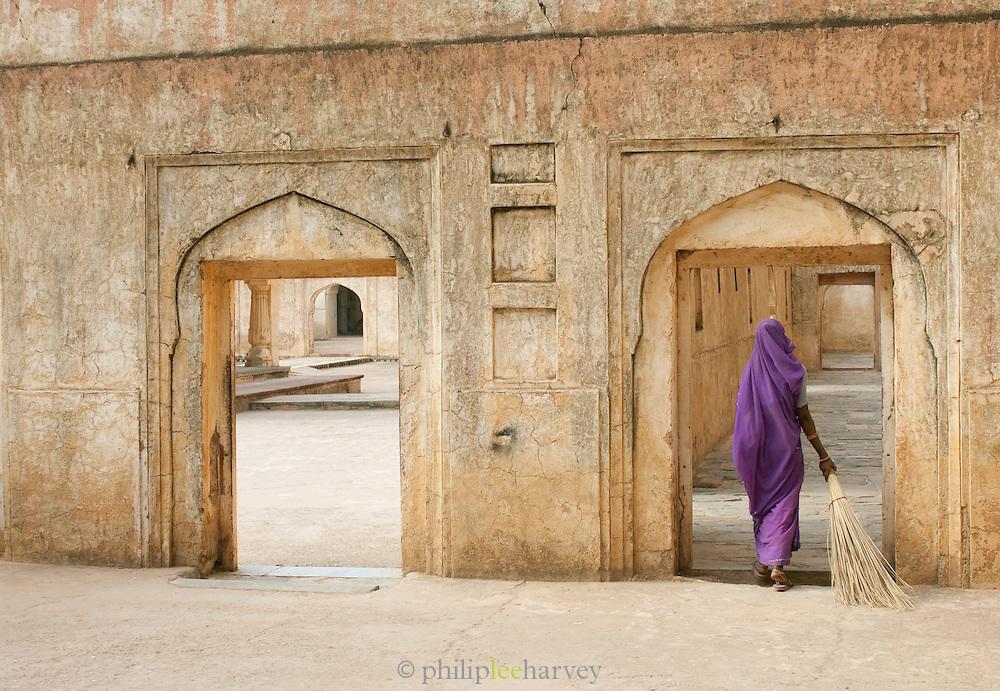 Groundswoman in sari walking through the Amber Fort near Jaipur, Rajasthan, India