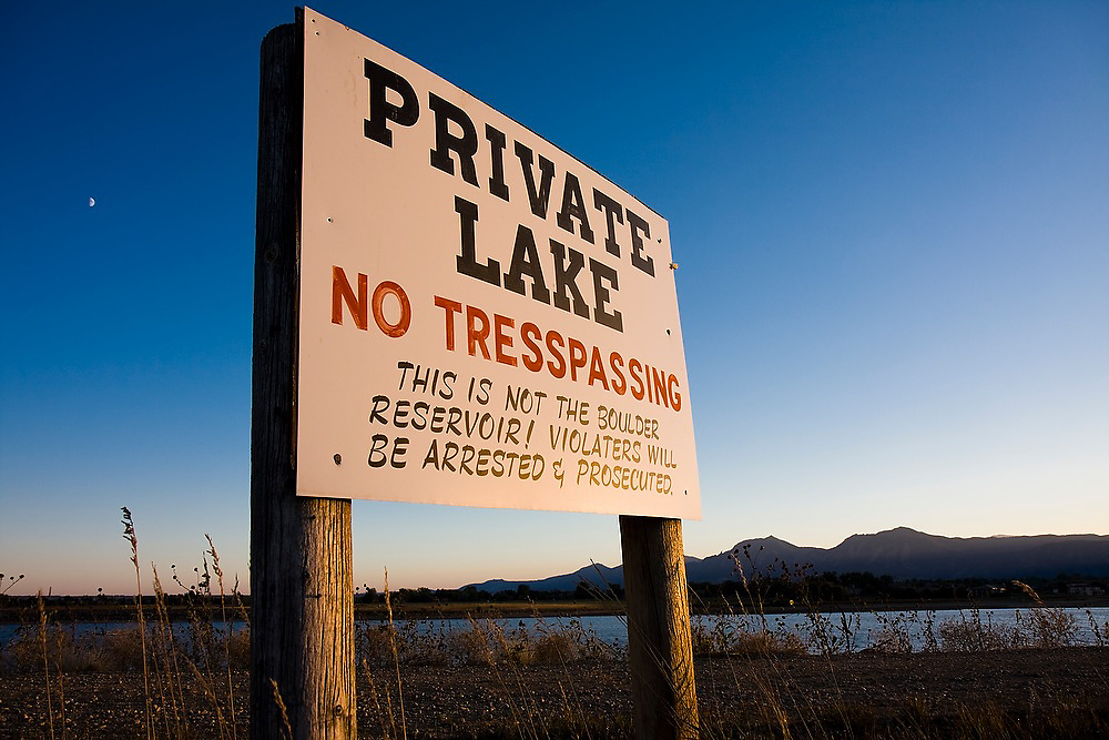 """A no trespassing sign for a """"Private Lake"""" warns that """"This is not the Boulder Reservoir"""" from its perch overlooking Boulder Reservoir outside Boulder, Colorado."""