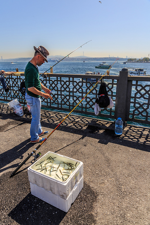 Istavrit (a.k.a. horse mackerel) fisherman and his catch on Galata Bridge in Istanbul, Turkey. Istavrit is a saltwater fish that is edible and can be smoked, fried, salted, and baked. It is an important commercial fish.