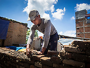 03 AUGUST 2015 - SANKHU, NEPAL: A man rebuilds a home destroyed by the earthquake in Sankhu, a community about 90 minutes from central Kathmandu. He is using bricks recycled from the original home and mud from the earthquake rubble as mortar.  The Nepal Earthquake on April 25, 2015, (also known as the Gorkha earthquake) killed more than 9,000 people and injured more than 23,000. It had a magnitude of 7.8. The epicenter was east of the district of Lamjung, and its hypocenter was at a depth of approximately 15 km (9.3 mi). It was the worst natural disaster to strike Nepal since the 1934 Nepal–Bihar earthquake. The earthquake triggered an avalanche on Mount Everest, killing at least 19. The earthquake also set off an avalanche in the Langtang valley, where 250 people were reported missing. Hundreds of thousands of people were made homeless with entire villages flattened across many districts of the country. Centuries-old buildings were destroyed at UNESCO World Heritage sites in the Kathmandu Valley, including some at the Kathmandu Durbar Square, the Patan Durbar Squar, the Bhaktapur Durbar Square, the Changu Narayan Temple and the Swayambhunath Stupa. Geophysicists and other experts had warned for decades that Nepal was vulnerable to a deadly earthquake, particularly because of its geology, urbanization, and architecture.    PHOTO BY JACK KURTZ