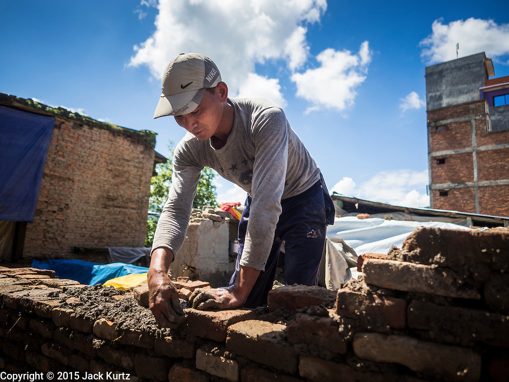 03 AUGUST 2015 - SANKHU, NEPAL: A man rebuilds a home destroyed by the earthquake in Sankhu, a community about 90 minutes from central Kathmandu. He is using bricks recycled from the original home and mud from the earthquake rubble as mortar.  The Nepal Earthquake on April 25, 2015, (also known as the Gorkha earthquake) killed more than 9,000 people and injured more than 23,000. It had a magnitude of 7.8. The epicenter was east of the district of Lamjung, and its hypocenter was at a depth of approximately 15km (9.3mi). It was the worst natural disaster to strike Nepal since the 1934 Nepal–Bihar earthquake. The earthquake triggered an avalanche on Mount Everest, killing at least 19. The earthquake also set off an avalanche in the Langtang valley, where 250 people were reported missing. Hundreds of thousands of people were made homeless with entire villages flattened across many districts of the country. Centuries-old buildings were destroyed at UNESCO World Heritage sites in the Kathmandu Valley, including some at the Kathmandu Durbar Square, the Patan Durbar Squar, the Bhaktapur Durbar Square, the Changu Narayan Temple and the Swayambhunath Stupa. Geophysicists and other experts had warned for decades that Nepal was vulnerable to a deadly earthquake, particularly because of its geology, urbanization, and architecture.    PHOTO BY JACK KURTZ