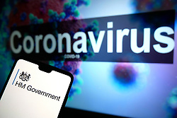 The HM Government logo seen displayed on a mobile phone with an illustrative model of the Coronavirus displayed on a monitor in the background. Photo credit should read: James Warwick/EMPICS Entertainment