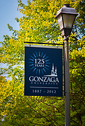 Gonzaga University is a private Roman Catholic university located in Spokane, Washington, United States. Founded in 1887 by the Society of Jesus, it is one of 28 member institutions of the Association of Jesuit Colleges and Universities and is named after the young Jesuit saint, Aloysius Gonzaga. The campus houses 105 buildings across 131 acres (437,000 m²) of grassland along the Spokane River, in a residential setting half a mile (800 m) from downtown Spokane. The university was founded by Father Joseph Cataldo, SJ, an Italian-born priest and missionary who wished to create a Catholic school in the Pacific Northwest for local Native Americans.