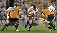 Photo: Richard Lane.<br />Australia v England. Rugby World Cup Final, at the Telstra Stadium, Sydney. RWC 2003. 22/11/2003. <br />England captain, Martin Johnson attacks as Justin Harrison and Nathan Sharpe square up to tackle.