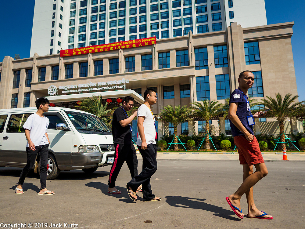 """15 FEBRUARY 2019 - SIHANOUKVILLE, CAMBODIA:  Chinese casino workers walk past Nanhai Pearl Hotel Apartment, a Chinese development in Sihanoukville. There are about 80 Chinese casinos and resort hotels open in Sihanoukville and dozens more under construction. The casinos are changing the city, once a sleepy port on Southeast Asia's """"backpacker trail"""" into a booming city. The change is coming with a cost though. Many Cambodian residents of Sihanoukville  have lost their homes to make way for the casinos and the jobs are going to Chinese workers, brought in to build casinos and work in the casinos.      PHOTO BY JACK KURTZ"""