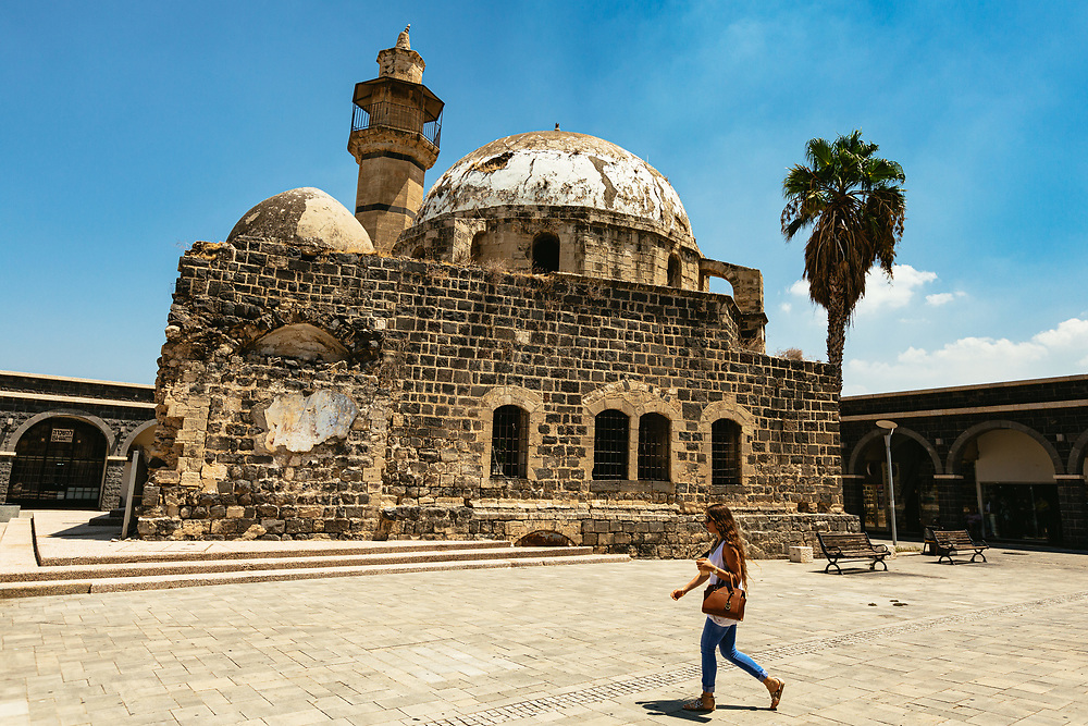 A woman walks past the Al Omari mosque in The Old City of Tiberias, northern Israel