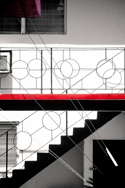 A MIami Modern railing and guy wires from a utility pole create a pattern on a Miami Beach apartment building.