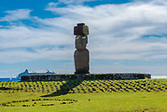 A large Moai statue with open eyes sits on top of an altar. A cruise ship is in the background. Editorial Use Only.