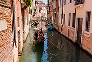 A gondolier rows his gondola along a canal on a warm summer day in Venice, Italy
