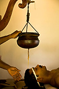 Sirodhara treatment is the rejuvenation process involved in pouring a continous flow of hot medicated oil from a clay pot onto the patient's head as part of the full Ayurveda treatment al Kalari Kovilakom, Kerala, India