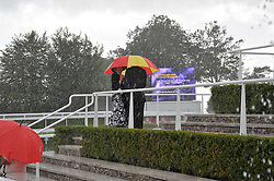 Race goers in the rain at the 3rd day of the 2009 Glorious Goodwood racing festival held at Goodwood Racecourse, West Sussex on 30th July 2009.