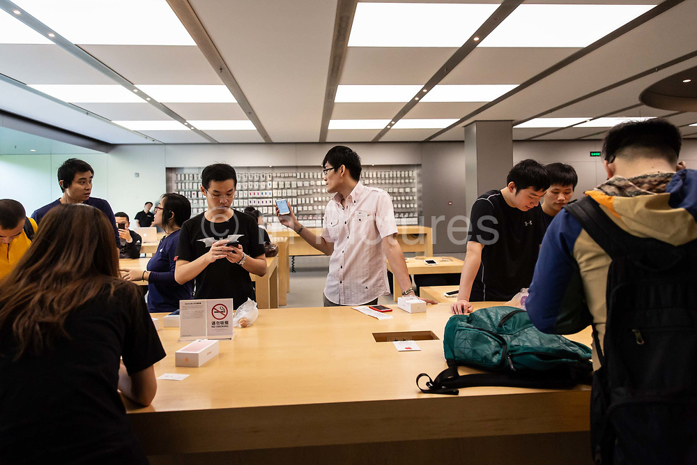 Customers look at an Apple Inc. iPhone 7 Plus smartphones at the Apple Store inside the IAPM shopping mall in Shanghai, China, on Friday, Sept. 16, 2016. iPhone sales are slowing in Chinas Apples second largest market, as local upstarts such as Huawei and Xiaomi are eating into the companys high end market.