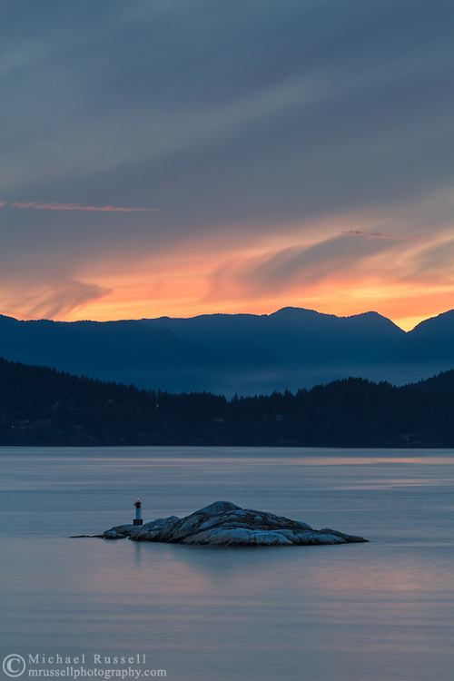 One of the Grebe Islets in Howe Sound.  Photographed at sunset from Juniper Point at Lighthouse Park in West Vancouver, British Columbia, Canada. In the background you can see Bowen Island, and the mountain peaks in the Sunshine Coast's Tetrahedron Range.