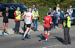 © Licensed to London News Pictures. 19/04/2019. Maidenhead, UK. Prime Minister THERESA MAY  helps out as a marshal with her husband PHILIP MAY (right), at the Maidenhead Easter 10 run in her constituency of Maidenhead in Berkshire. Parliament currently on Easter recess after an extension to Article 50 was granted by the EU. Photo credit: Ben Cawthra/LNP