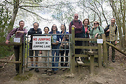 Portrait line-up of friends in a local ramblers club, standing at a countryside stile and gate.