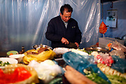 A food stall owner prepare dishes for customers at a night market in Chuzhou, Anhui Province, China on 02 March, 2011.  Chuzhou is the city where Dongdaxu Village is located, the ancestral home of current Chinese vice premier Li Keqiang, slated to be the next premier and the man in charge of China's economic transformation.