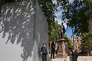A week after a Black Lives Matter protest turned to violence when the statue of wartime Prime Minister Sir Winston Churchill was daubed in graffiti which called him a racist, and despite warning from police not to attend protests at all today - and to be off the streets by 5.00pm - a large group crowd of right-wing groups gathered at the boxed-in statue to protect it from further vandalism by Black Lives Matter and anti-racism opponents. Alongside the statue of Sir Robert Peel, the founder of the modern police force, Met Police officers also guarded the boxed-in statue of Nelson Mandela which the far-right had said they would attack, on 13th June 2020, in London, England.
