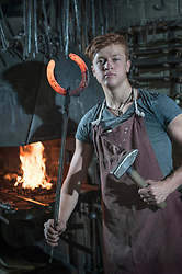 Apprentice blacksmith with hammered red hot horseshoe at workshop, Bavaria, Germany