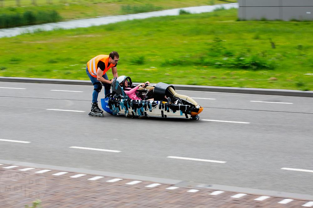 Aniek Rooderkerken zit in de Velox. Op een weg op de campus van de TU Delft oefent het team met het rijden in een Velox. In september wil het Human Power Team Delft en Amsterdam, dat bestaat uit studenten van de TU Delft en de VU Amsterdam, tijdens de World Human Powered Speed Challenge in Nevada een poging doen het wereldrecord snelfietsen voor vrouwen te verbreken met de VeloX 7, een gestroomlijnde ligfiets. Het record is met 121,44 km/h sinds 2009 in handen van de Francaise Barbara Buatois. De Canadees Todd Reichert is de snelste man met 144,17 km/h sinds 2016.<br /> <br /> With the VeloX 7, a special recumbent bike, the Human Power Team Delft and Amsterdam, consisting of students of the TU Delft and the VU Amsterdam, also wants to set a new woman's world record cycling in September at the World Human Powered Speed Challenge in Nevada. The current speed record is 121,44 km/h, set in 2009 by Barbara Buatois. The fastest man is Todd Reichert with 144,17 km/h.