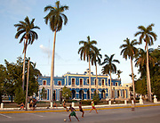 Cuban Young men boys playing football in the street outside a municipal building fringed by palm trees, Cienfuegos province, Cuba. .