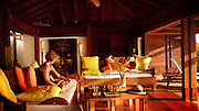 A woman reads and lounges in a beautiful tropical resort hotel room.