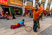 A Tibetan woman and man prostrate themselves, as other pilgrims circumambulate The Barkhor (the route around the most sacred temple in Tibet, the Jokhang Temple), Lhasa, Tibet (Xizang), China.