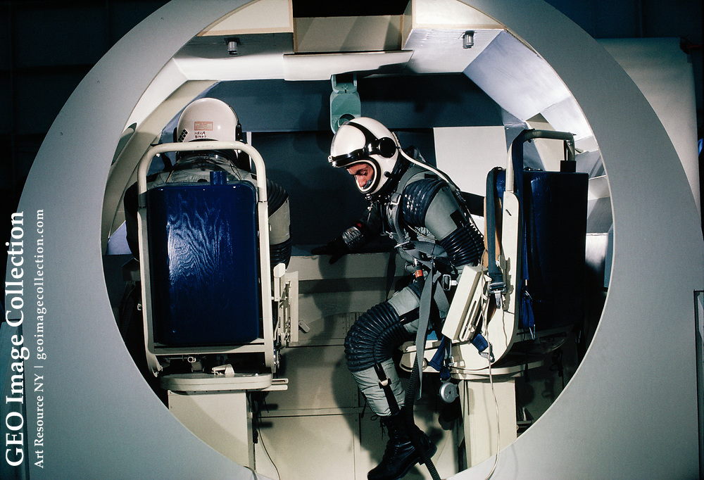 Space-suited test person practices maneuvers inside a training vehicle, while another man sits in the trainer's chair.