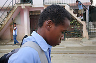 """Robinson Martinez, 15, walks home after school in Santiago, Dominican Repbulic. In the mornings he attends Acción Callejera (Street Action), an organization dedicated to helping child laborers and give them a new purpose in life. Robinson had stopped attending school, but was able to re-enter with the help of Acción. When Robinson first arrived to the center they called him """"zero tolerance,"""" because he was so aggressive with the other children that even the slightest touch or taunt made him explode. In a years time he has become affectionate with the staff and has been transformed into a leader. Accion prepares kids to go back to school, provides hot meals for a symbolic fee, field trips, and free medical care and counseling. """"All I had in my heart was an emptiness when I arrived here, now it is full,"""" says Robinson. Sara A. Fajardo/Catholic Relief Services"""