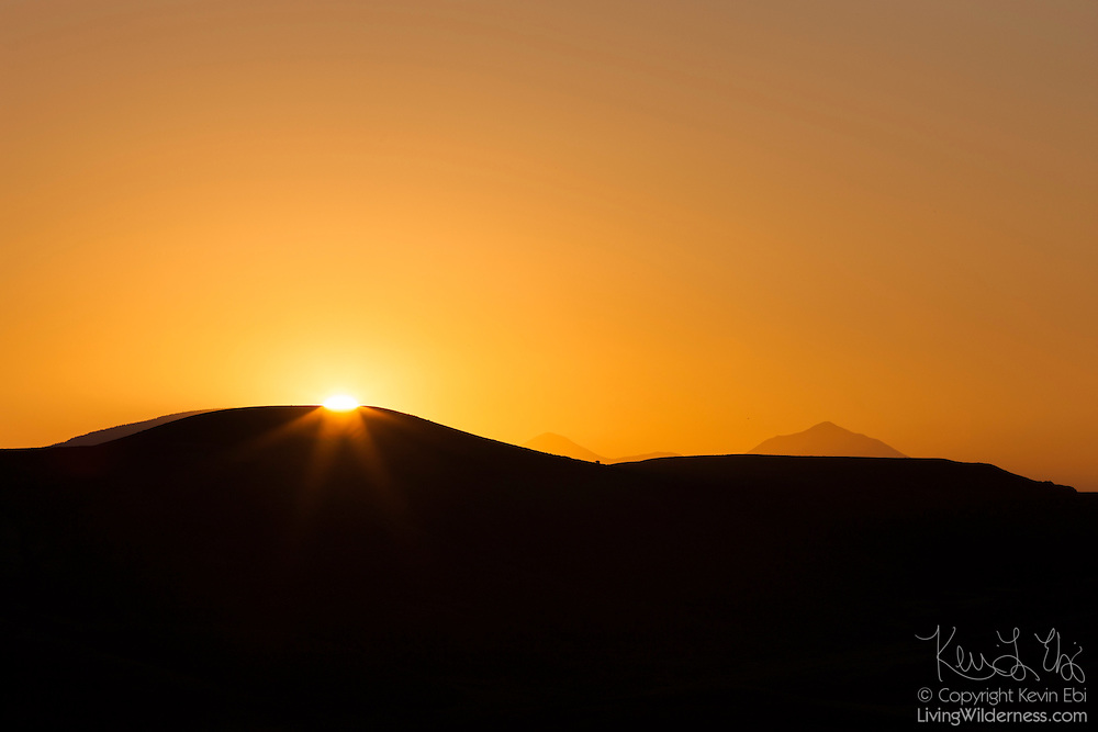 The sun rises over Tenderfoot Mountain, a 8625 foot (2629 meter) peak in Gunnison, Colorado. Two taller mountains in Gunnison County are visible on the horizon. At center is Quartz Dome, which is 11299 feet (3444 meters) tall. At right is Lookout Mountain, which is 11099 feet (3383 meters) tall.