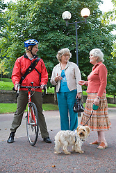 Cyclist and two women talking in the park,