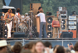 Phil changing a broken string on his instrument as the roadies look on...  The Grateful Dead play Raceway Park, Englishtown NJ, 3 September 1977