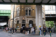 The Globe pub in Borough Market selling takeaway drinks to a queue of people who congregate outside under coronavirus lockdown on 1st July 2020 in London, England, United Kingdom. Pubs have used this technique to remain in business to a degree while they are not allowed to open. As the July deadline approaces and government will relax its lockdown rules further, the central London remains very quiet, while some non-essential shops are allowed to open with individual shops setting up social distancing systems.