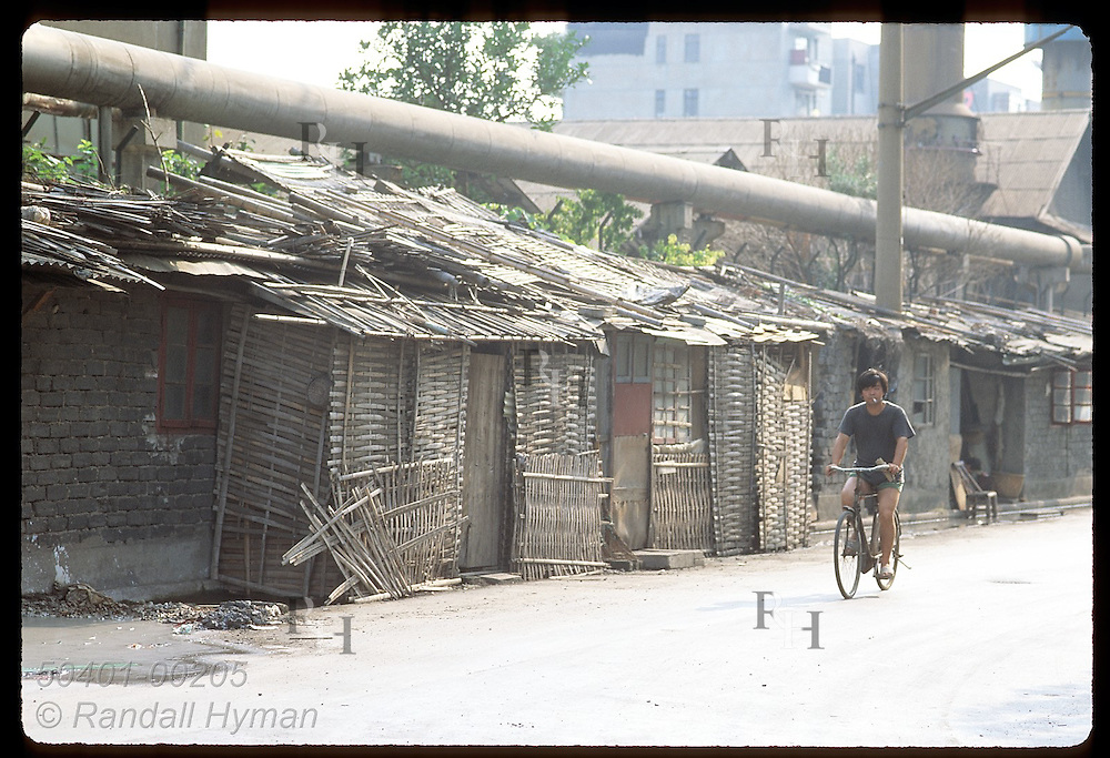 Young man bikes past line of bamboo shacks in an industrial area where many poor live; Shanghai. China
