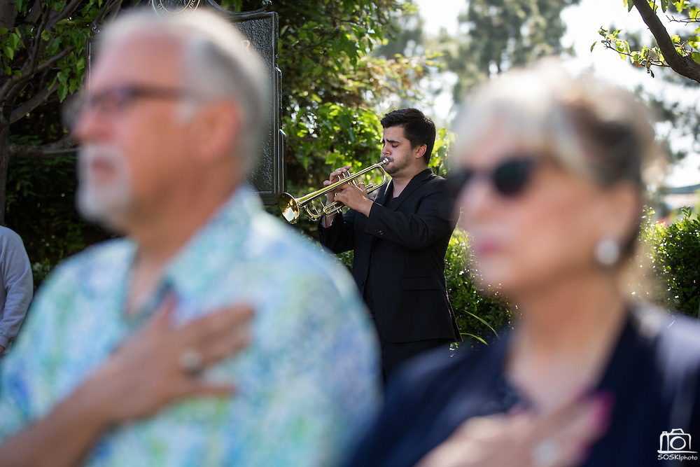 Aaron Montoya of San Francisco performs TAPS as attendees cover their hearts with their hands during the City of Milpitas Memorial Day ceremony at Milpitas City Hall in Milpitas, California, on May 30, 2016. (Stan Olszewski/SOSKIphoto)