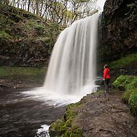 Female hiker stands near Sgwd yr Eira Waterfall - River Hepste, near Ystradfellte, Brecon Beacons national park, Wales