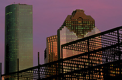 Stock photo of steel beams of a construction site crossing the downtown Houston skyline at dusk.