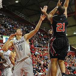 Rutgers Scarlet Knights forward/center Austin Johnson (21) hooks a shot over Connecticut Huskies forward Tyler Olander (10) and Connecticut Huskies center Andre Drummond (12) during Rutgers' 67-60 upset victory over #8 UConn in NCAA Big East Basketball action at the Louis Brown Athletic Center in Piscataway, N.J. on Jan 7, 2012.