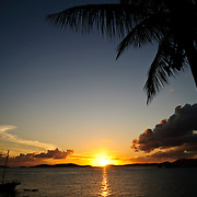 A beautiful sunset in the Caribbean with a palm tree and sailing boat silhoetted against the setting sun.