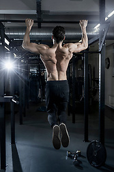 Shirtless muscular man doing chin-ups exercise at the gym