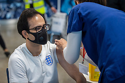 © Licensed to London News Pictures. 20/06/2021. LONDON, UK.  A man wearing an England football shirt receives his Pfizer vaccine jab at a mass vaccination centre at Tottenham Hotspur stadium as the capital aims for 100,000 doses administered per day. Chelsea, West Ham and Charlton were other London football clubs who took part the previous day. With cases of the Delta variant increasing, the UK government has invited all over 18s for a Covid-19 vaccination in an effort to have as many people to be vaccinated by July 19th, the revised date when all lockdown restrictions are relaxed.  Photo credit: Stephen Chung/LNP