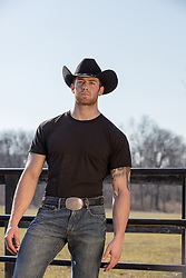 hot cowboy by a fence
