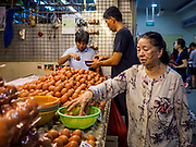 09 JULY 2017 - SINGAPORE: A woman shops for eggs in Tiong Bahru market, in the midst of the Tiong Bahru Housing estate, was the first indoor market in Singapore and is considered one of the best markets in Singapore. It was built in 1955 in an effort to organize vendors and get them off the neighborhood streets. Tiong Bahru neighborhood is now one of the most popular neighborhoods in Singapore for both expats and Singaporeans.    PHOTO BY JACK KURTZ