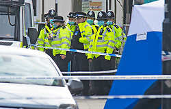 © Licensed to London News Pictures 11/04/2021. Sydenham, UK. A group of police officers. A Met Police investigation has been launched after a 17 year old male was fatally stabbed in Sydenham, South East London last night. A forensic tent can be seen with a large police cordon in place this morning. Photo credit:Grant Falvey/LNP