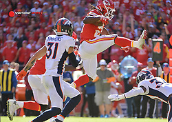 Oct 28, 2018; Kansas City, MO, USA; Kansas City Chiefs running back Kareem Hunt (27) leaps over Denver Broncos defensive back Will Parks (34) during the second half at Arrowhead Stadium. Mandatory Credit: Denny Medley-USA TODAY Sports