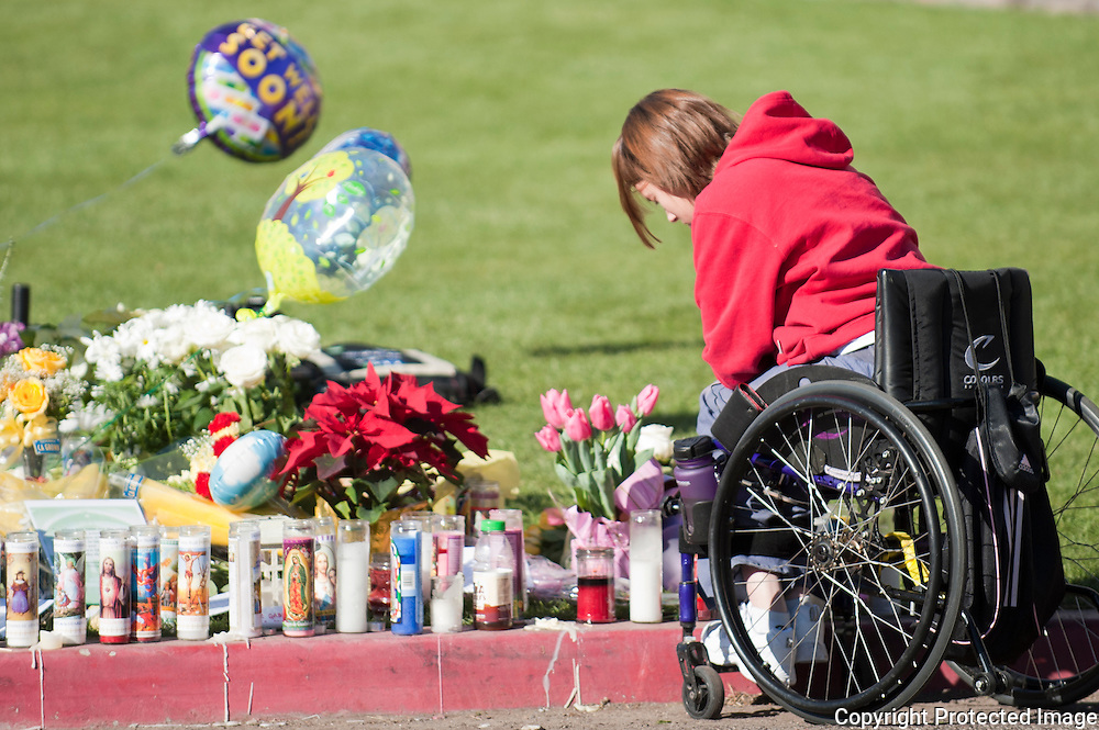 A young woman reads some of the words left by some of the visitors to the memorial.