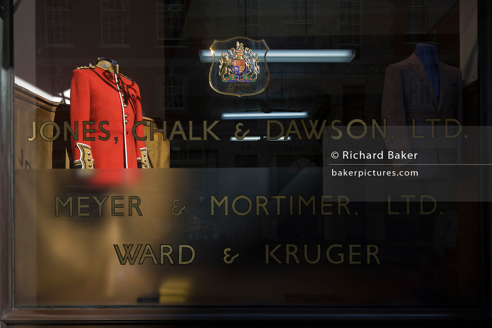 A formal military dress uniform and a civilian jacket on display in a london's taylor's premises in Sackville Street, London. Jones Chalk & Dawson have well over a century of fine tailoring tradition. The company commenced trading in 1896 when William Jones broke away from Hawkes of Savile Row (later Gieves and Hawkes), where he was head military cutter. Joseph H Dawson and Arthur Chalk also worked at Hawkes. In 1902 the young company were soon a Royal appointment from HRH the Prince of Wales, later King George V. In 1940 they were appointed by King George VI and today, Jones Chalk & Dawson continue to hold a warrant to the Belgian Royal Family.
